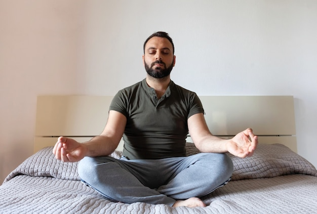 Man mediteren op bed thuis.
