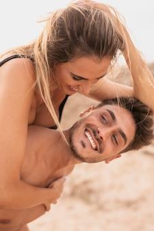 Man meeliften rit vriendin op strand