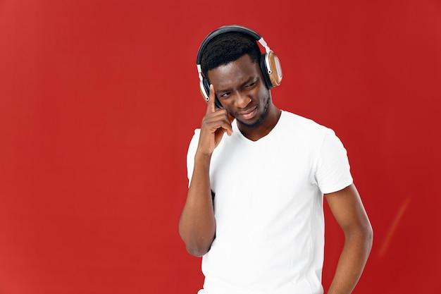 Man met afrikaans uiterlijk in koptelefoon naast technologieklok