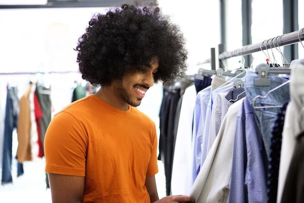 Man met afro op zoek naar kleding in de winkel
