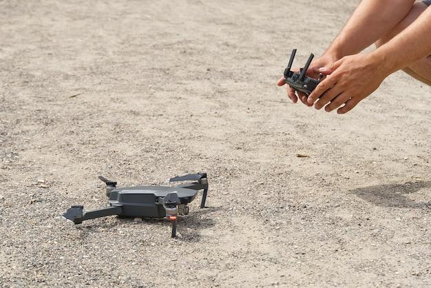 Man met afstandsbediening om drone te bedienen, wijst wazig land toe.