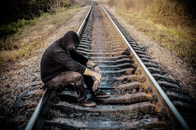 Man met alcohol op spoorlijnen buitenshuis. reisconcept. eenzaam persoon. zelfmoordconcept. depressie ziekte.