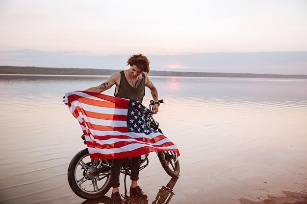 Man met amerikaanse vlag in de woestijn die zich in de buurt van motorfiets bevindt