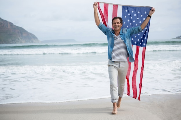 Man met amerikaanse vlag op strand