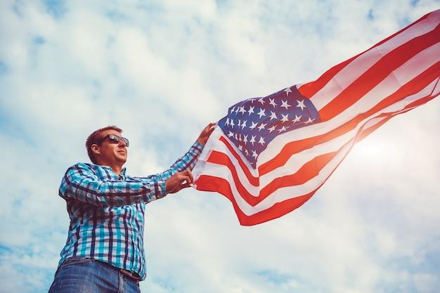 Man met amerikaanse vlag tegen de bewolkte hemel