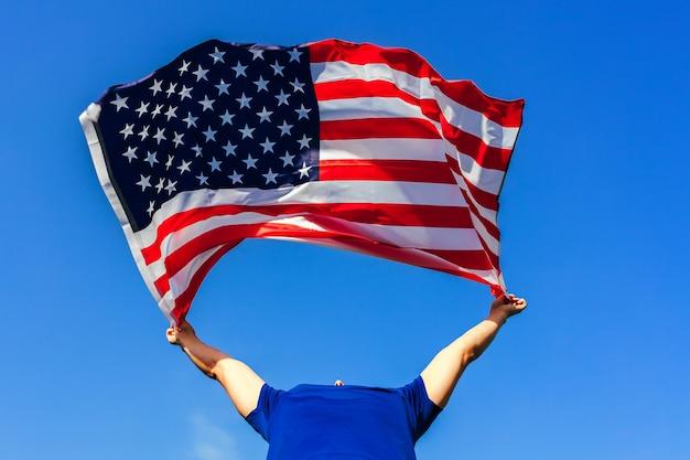 Man met amerikaanse vlag tegen de blauwe lucht