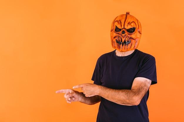 Man met angstaanjagend pompoenlatexmasker met blauw t-shirt, wijzend naar de linkerkant met zijn handen naar de kopieerruimte, op een oranje achtergrond. halloween en dagen van het dode concept.