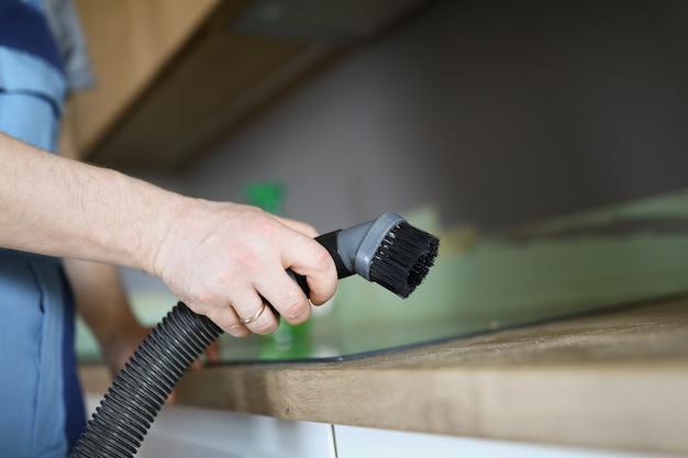 Man met apparatuur voor het reinigen van bouwstof