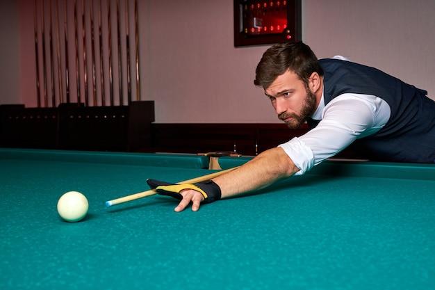 Man met arm op biljarttafel, snookerspel spelen of voorbereiden om poolballen te schieten. sport spel snooker biljart