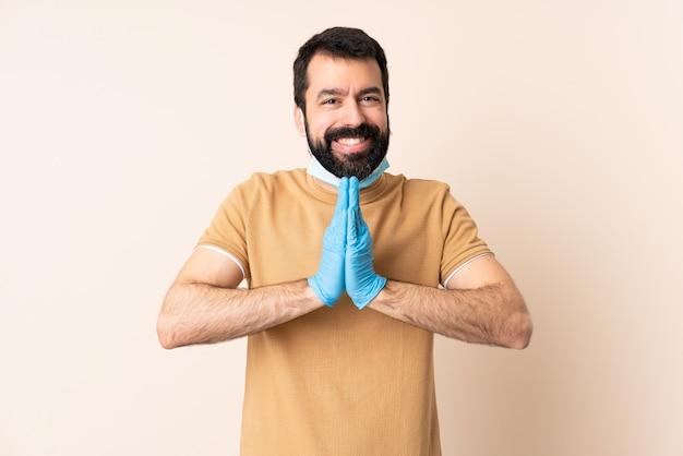 Man met baard beschermen tegen het coronavirus met een masker en handschoenen over geïsoleerde muur houdt palm bij elkaar. persoon vraagt iets