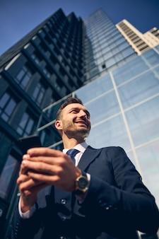 Man met baard die buiten naast het grote zakencentrum blijft en glimlacht