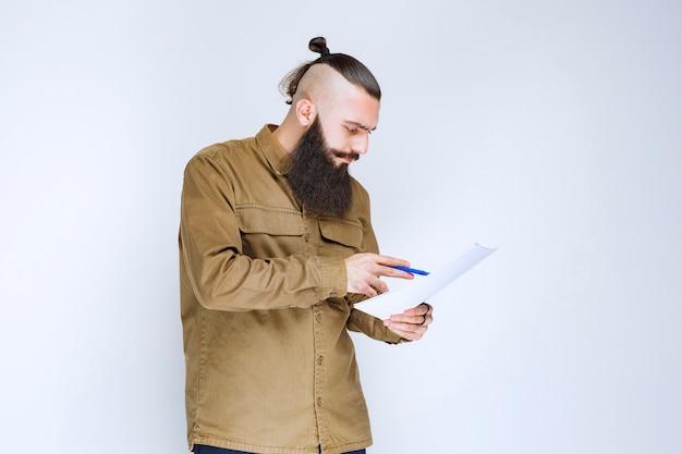 Man met baard die de projectlijst controleert en notities of correcties markeert.