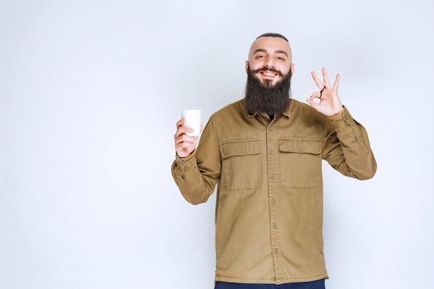 Man met baard die een kopje koffie vasthoudt en geniet van de smaak.