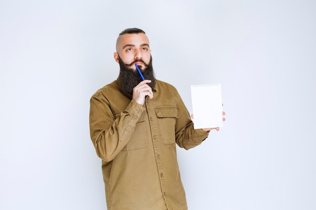 Man met baard die een quizpapier vasthoudt en er verward en attent uitziet.