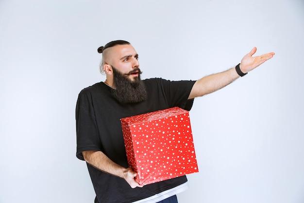 Man met baard die een rode geschenkdoos vasthoudt en ruzie maakt met iemand.