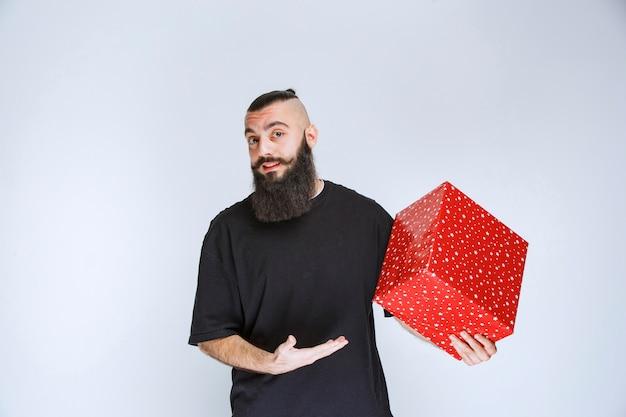 Man met baard die een rode geschenkdoos vasthoudt