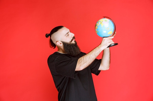 Man met baard die een wereldbol vasthoudt en er plaatsen overheen zoekt.