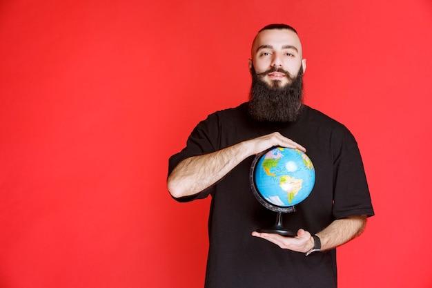 Man met baard die een wereldbol vasthoudt.