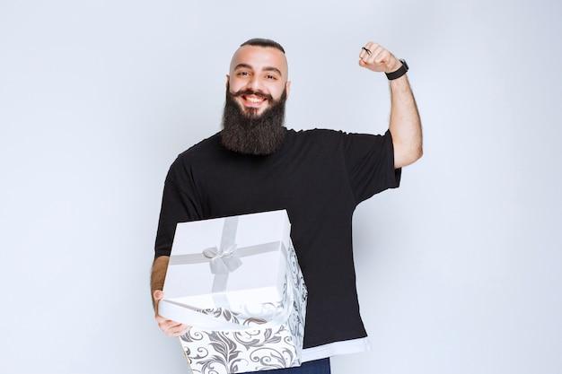 Man met baard die een witblauwe geschenkdoos vasthoudt en zich succesvol voelt.