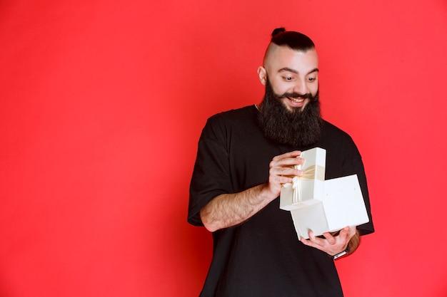 Man met baard die een witte geschenkdoos vasthoudt en deze met opwinding opent.