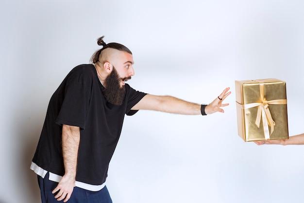 Man met baard die ernaar verlangt om een gouden geschenkdoos aan te nemen die hem wordt aangeboden.
