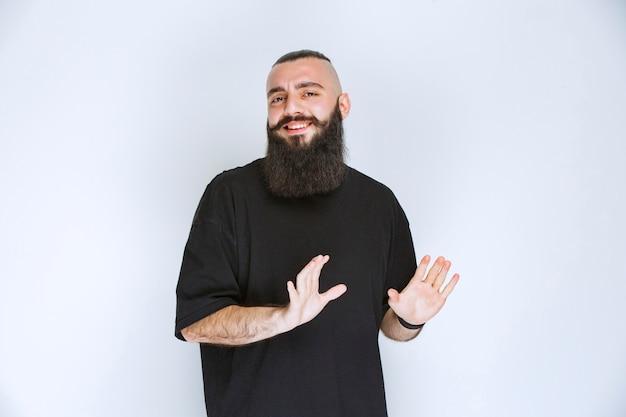 Man met baard die iets met open hand stopt.
