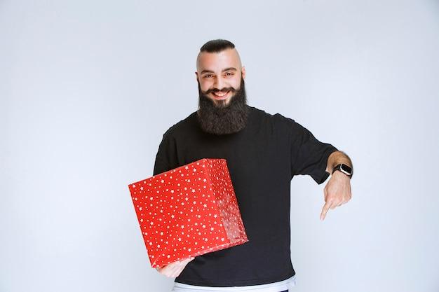 Man met baard die rode geschenkdoos aanbiedt