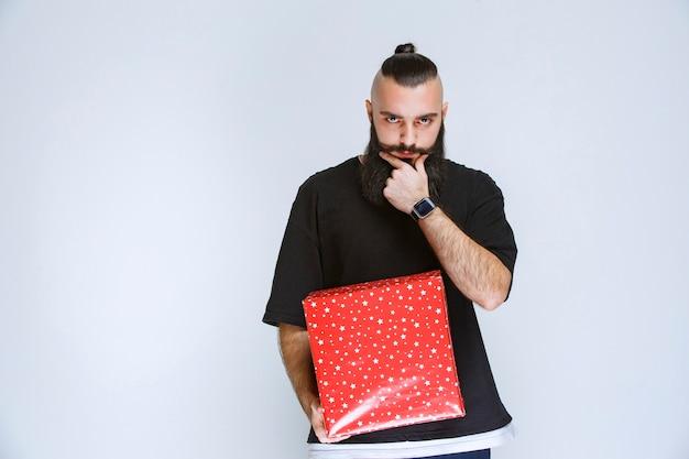 Man met baard die rode geschenkdozen vasthoudt en aarzelt om een keuze te maken.