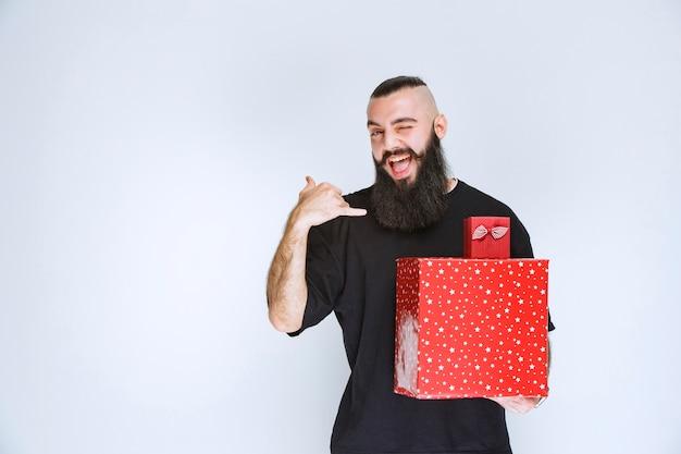 Man met baard die rode geschenkdozen vasthoudt en naar achteren wijst.