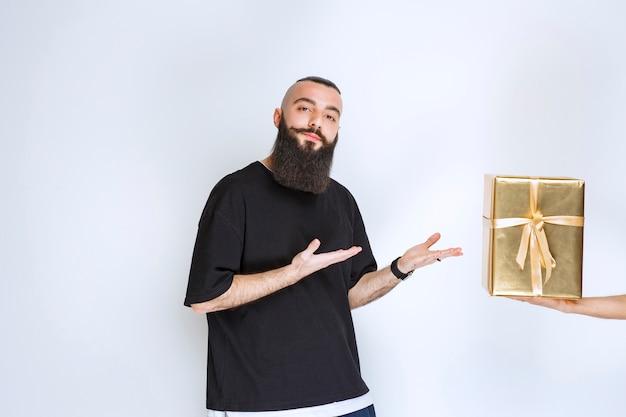 Man met baard die zijn gouden omslaggeschenkdoos toont.