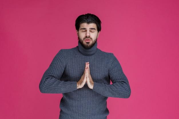 Man met baard die zijn handen vasthoudt op een manier alsof hij bidt of iets wenst.