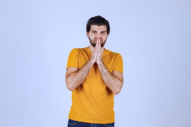 Man met baard die zijn handen verenigt en bidt en om iets vraagt