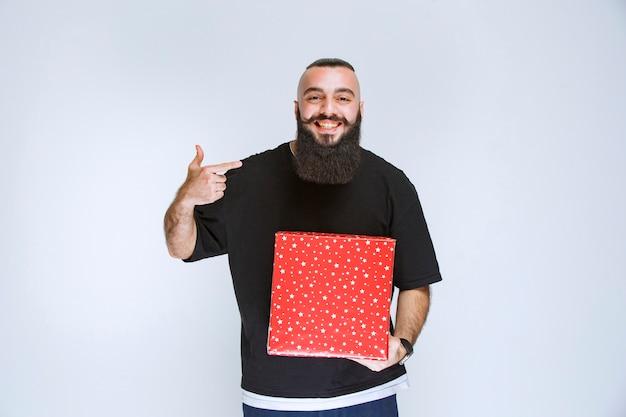 Man met baard die zijn rode geschenkdoos toont.