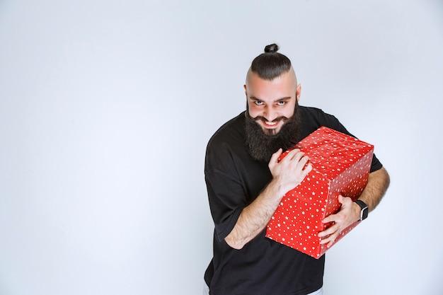 Man met baard die zijn rode geschenkdoos vasthoudt, ervan geniet en zich gelukkig voelt.