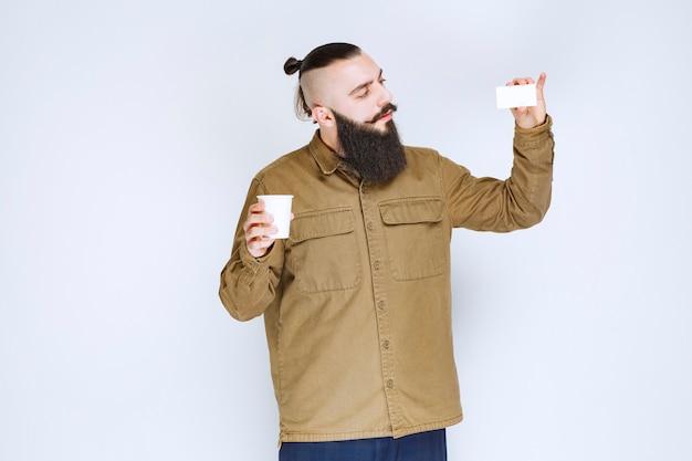 Man met baard die zijn visitekaartje laat zien terwijl hij een kopje koffie vasthoudt.