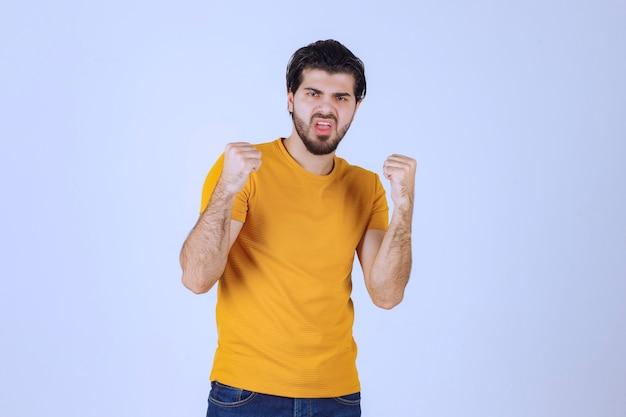 Man met baard die zijn vuist- en armspieren demonstreert en zich krachtig voelt