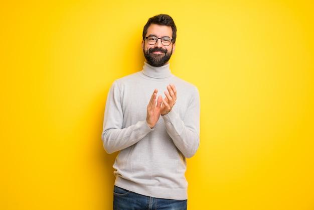 Man met baard en coltrui applaudisseren na presentatie in een conferentie