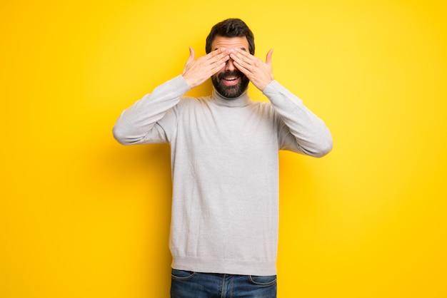 Man met baard en coltrui die de ogen bedekken met de handen. verrast om te zien wat er gaat gebeuren