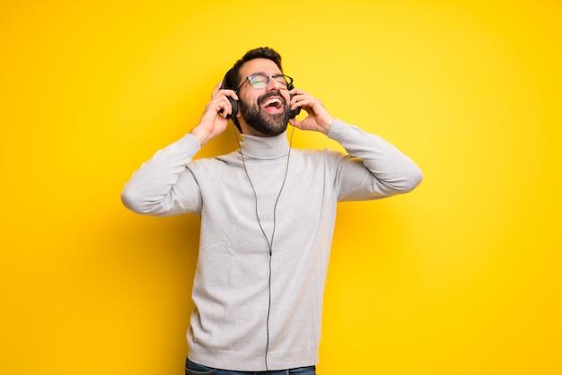 Man met baard en coltrui luisteren naar muziek met een koptelefoon