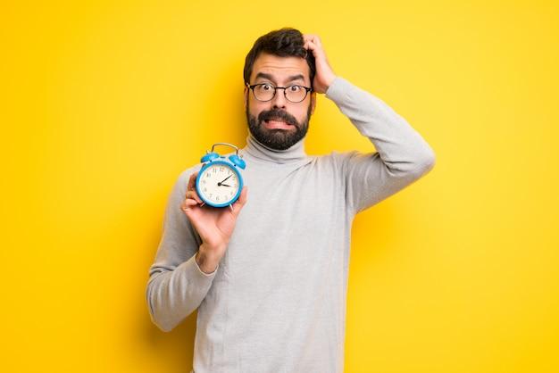 Man met baard en coltrui rusteloos omdat het te laat is geworden en met een vintage wekker
