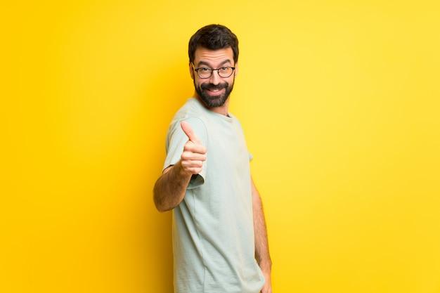Man met baard en groen shirt geven een duim omhoog gebaar omdat er iets goeds is gebeurd