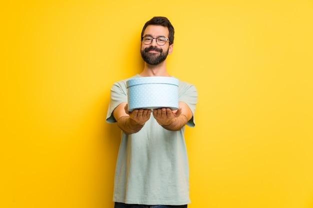 Man met baard en groen shirt met een geschenk in handen