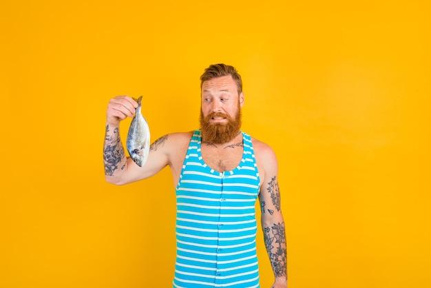 Man met baard en zwembroek ving een vis