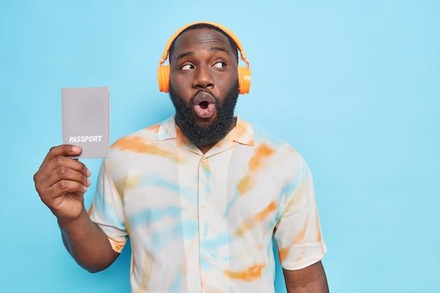 Man met baard houdt paspoort vast kijkt verrassend weg luistert naar muziek via koptelefoon nonchalant gekleed