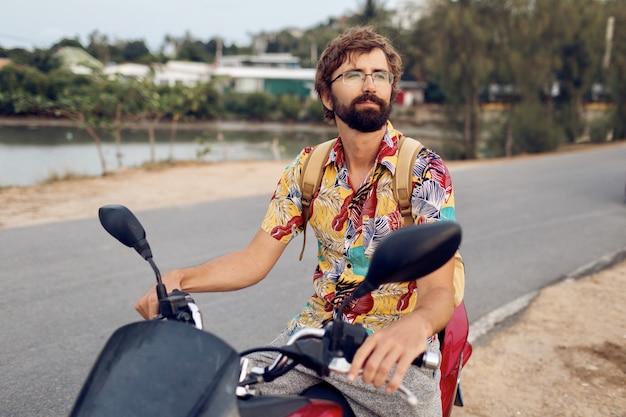 Man met baard in kleurrijke tropische shirt zittend op motor