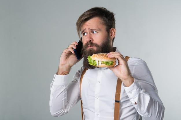 Man met baard in wit overhemd en bretels die junkfood eten van een fastfood-hamburger of cheeseburger en aan de telefoon praten op een grijze achtergrond