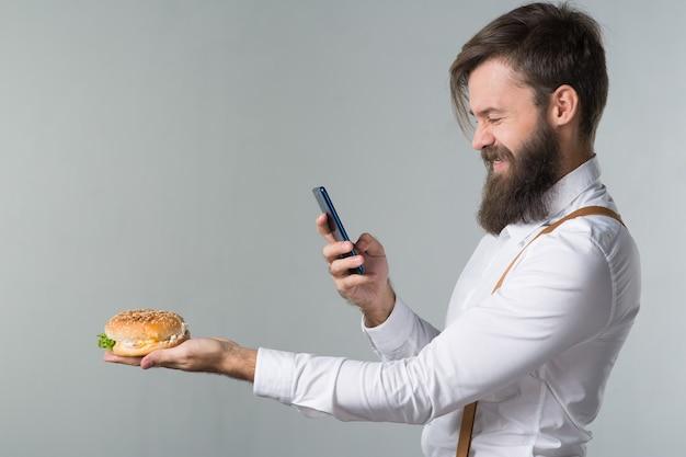 Man met baard in wit overhemd en bretels die junkfood eten van een fastfood-hamburger of cheeseburger en foto's van voedsel op de smartphone op grijze achtergrond