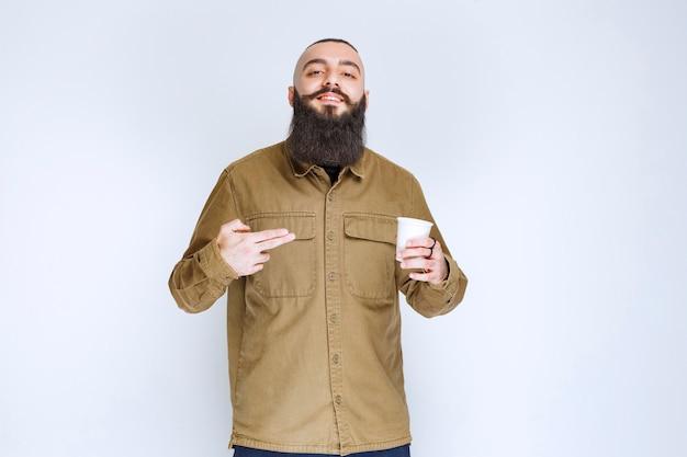 Man met baard met een kopje koffie in een wegwerpbeker.