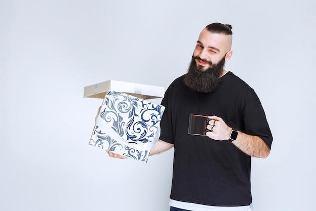 Man met baard met een open blauwe geschenkdoos met een kopje koffie en ziet er gelukkig uit.