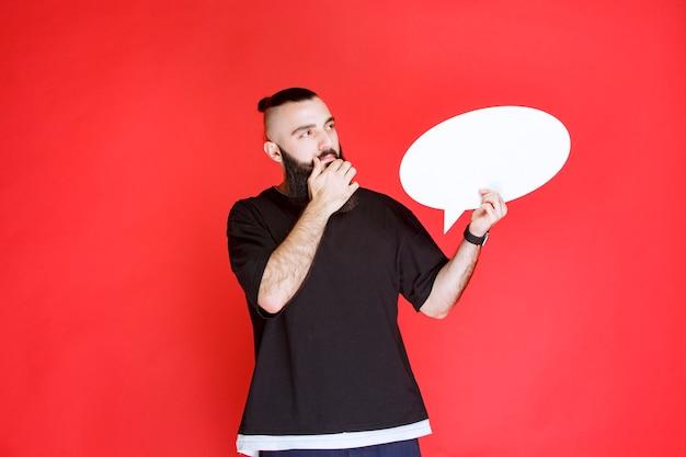 Man met baard met een ovale denkbord en brainstormen.